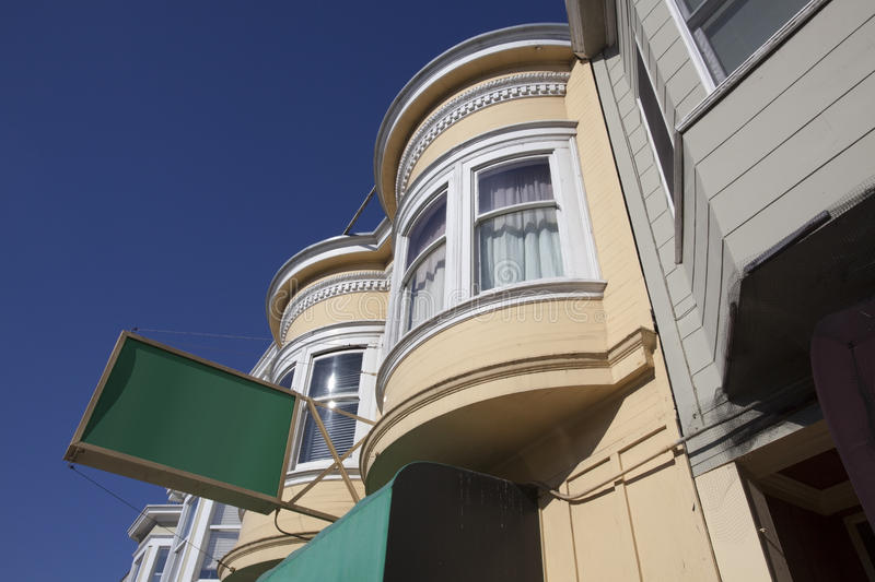 Windows with Sign. Traditional San Francisco, California Victorian style bay windows against blue sky with blank green sign royalty free stock image