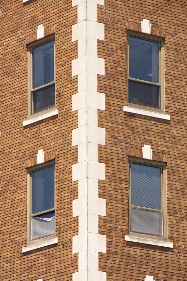 Windows sur la construction de brique de Brown photos stock