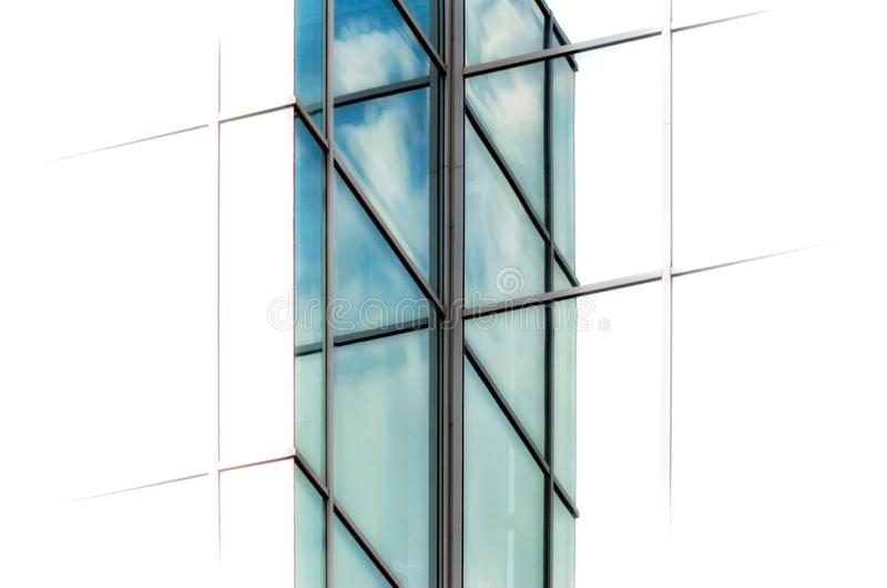 Windows of a tall business office building with reflection of sky and clouds on a white background in isolation stock photo