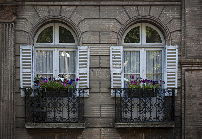 Windows in Toulouse. Two windows with shutters and wrought iron window boxes or balconies in a brick building in Toulouse, France stock photo