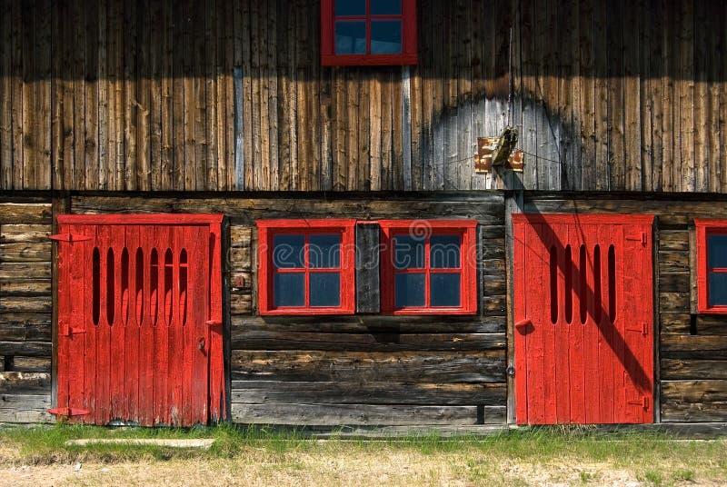 Windows vermelho resistido e porta em um celeiro imagem de stock