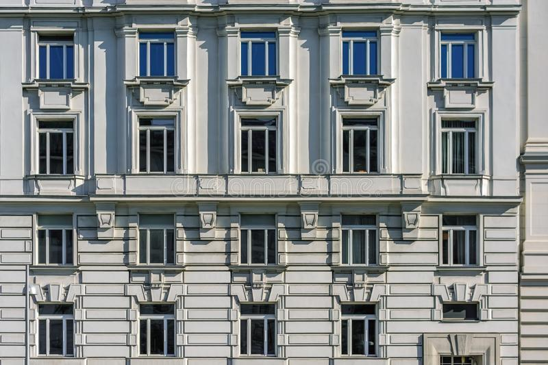 Windows on the wall. Rectangular windows on the facade of a gray building with a bas-relief royalty free stock image