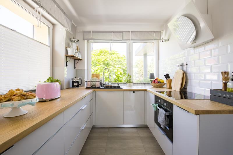 Windows in white kitchen interior with grey cabinets and wooden stock photos