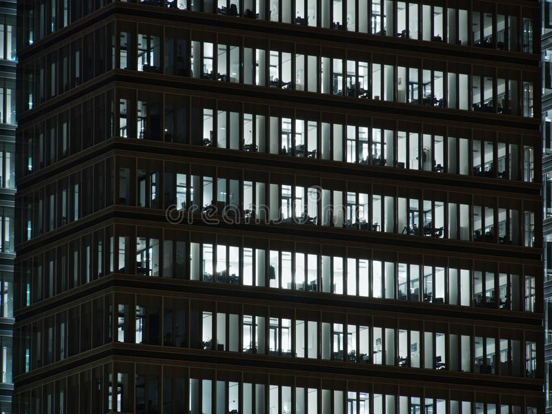 Windows of white lit offices in tall Office building. Viewed from outside royalty free stock photo