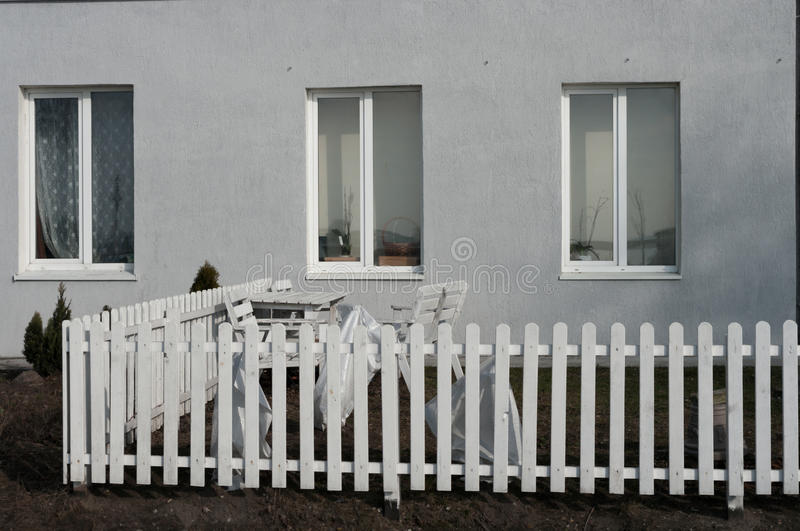 Windows, a white picket fence and garden furniture near the house. Windows,white picket fence and garden furniture near the house royalty free stock photography