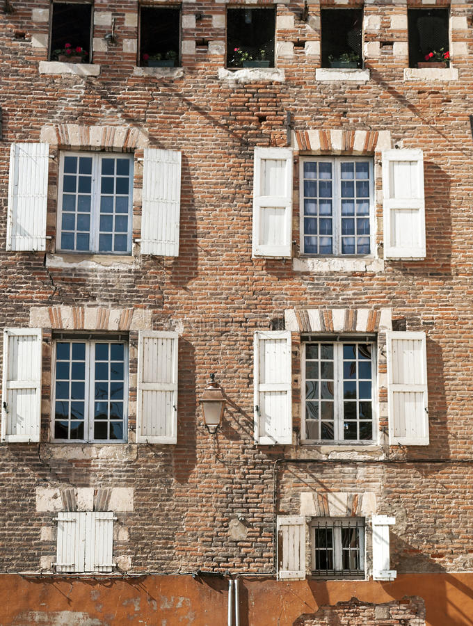 Windows with white shutters. On a brick wall on a sunny day, is an image vertically stock images