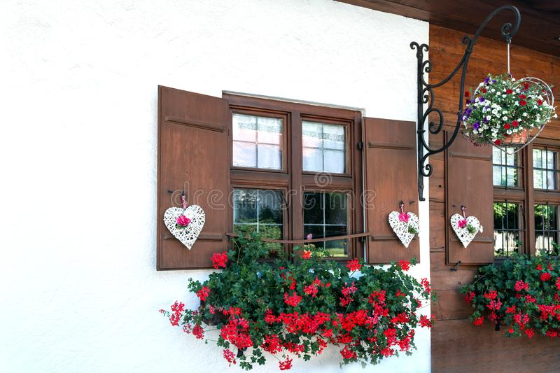 The windows of the wooden house are beautifully decorated with white hearts and flowers stock photography