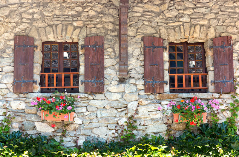 Windows with wooden shutters. Traditional windows in France with wooden shutters and planted flower troughs. This image was taken in Yvoire on the southern bank stock photography