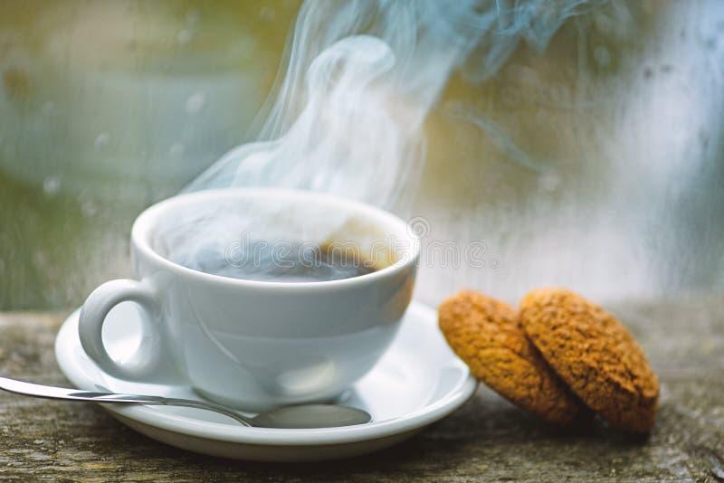 Свежий заваренный кофе в белых чашке или кружке на windowsill Влажные стеклянное окно и чашка горячего напитка кофеина Напиток ко стоковое изображение rf