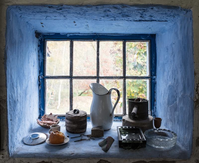 Windowsill still life with vintage objects framed by blue walls stock photos