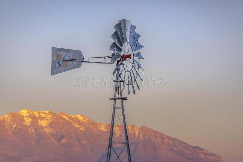 Windpump με ένα τραχύ χρυσό βουνό και ένα νεφελώδες υπόβαθρο ουρανού στοκ φωτογραφία με δικαίωμα ελεύθερης χρήσης