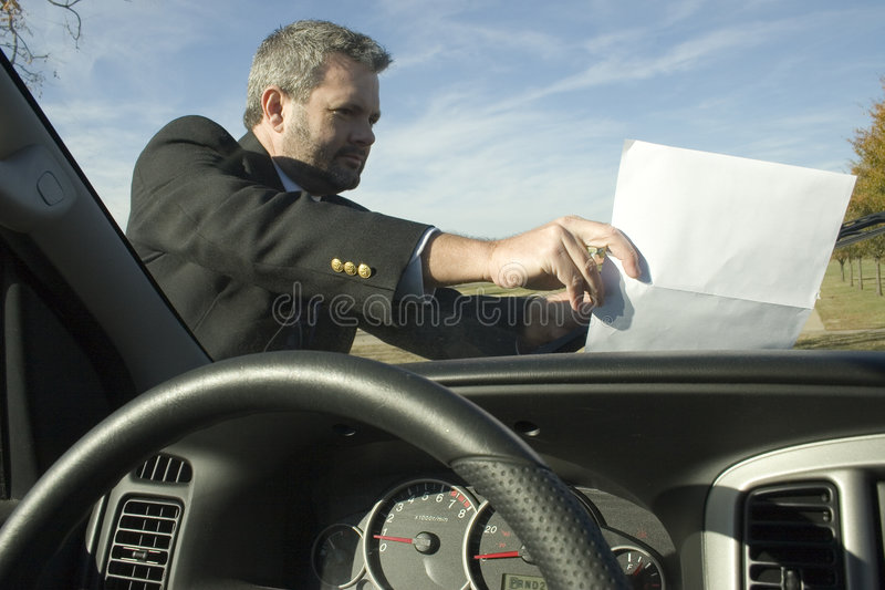 Windshield Flyer. Fourty something business man putting or taking flyer from car windshield royalty free stock photo