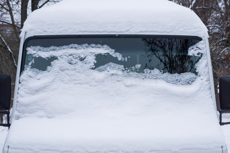 The windshield of the frozen minibus is covered with ice and snow on a winter day. stock photography