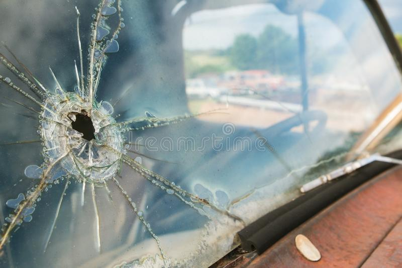 Windshield Of Junkyard Vehicle Has Hole And Cracks In Glass. The windshield of a junkyard vehicle is cracked and splintered from what appears to be a bullet hole stock image