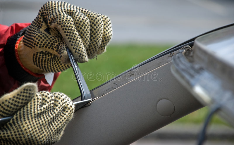 Windshield Repair. A worker cutting through adhesive before replacing the windshield. Selective focus on the end of the knife stock images