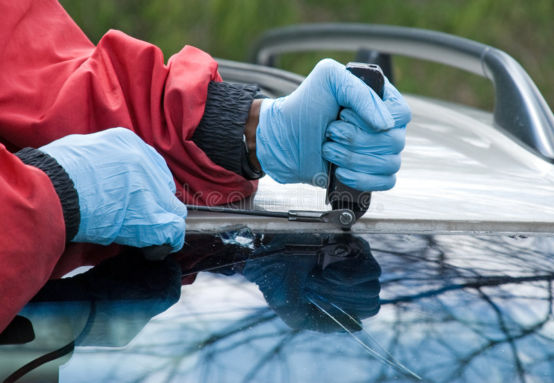 Windshield Repair. A worker slices through plastic molding and adhesive to remove a broken windshield