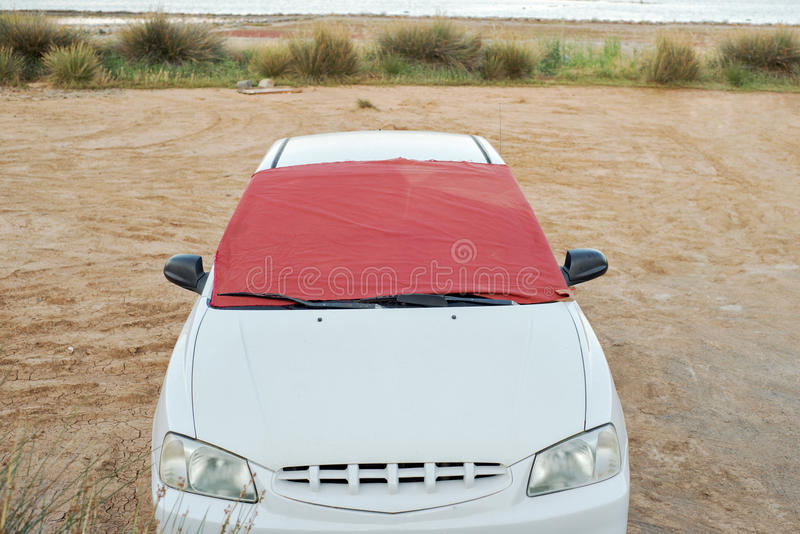 Windshield of white car covered by piece of fabric. Elounda, Crete, Greece - June 16, 2017: Windshield of white car covered by piece of fabric ,window sun shade stock images