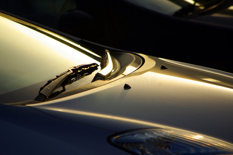 Windshield Wiper. Detail of a car windshield wipers lit by low sunlight royalty free stock image