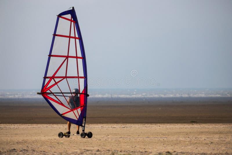 Windskate op het strand die in het zand lopen stock afbeeldingen