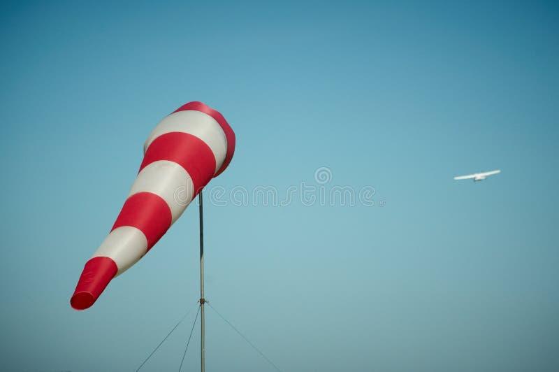Windsock дунутый ветром с самолетом на предпосылке стоковые фото