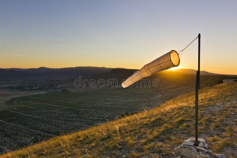Windsock no por do sol nas montanhas contra o sol foto de stock