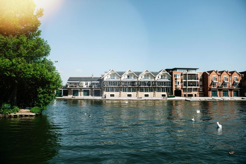 Thames river in Windsor. WINDSOR, BERKSHIRE, UNITED KINGDOM - MAY 19, 2018: Luxury houses on Tamisa river with swans and blue clear sky royalty free stock photos
