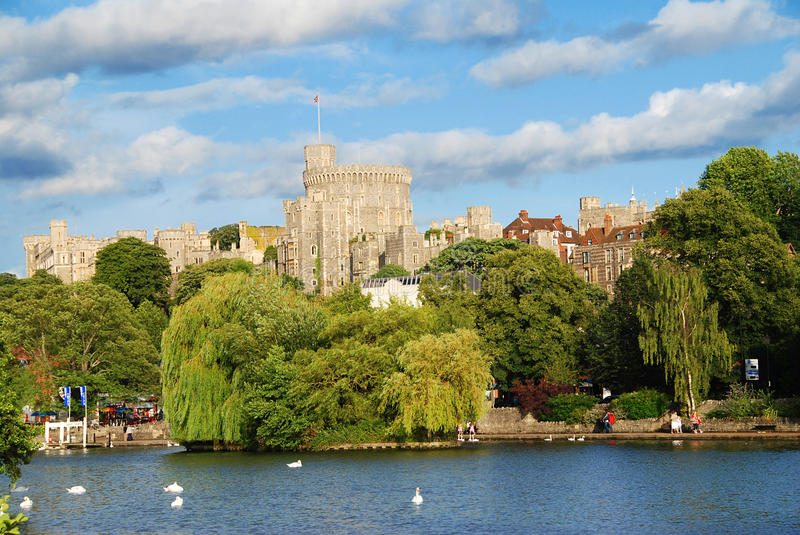 Windsor castle. Panorama of the mighty Windsor castle, the home of the Queen, with the river Thames and boat trips docks in the foreground royalty free stock images