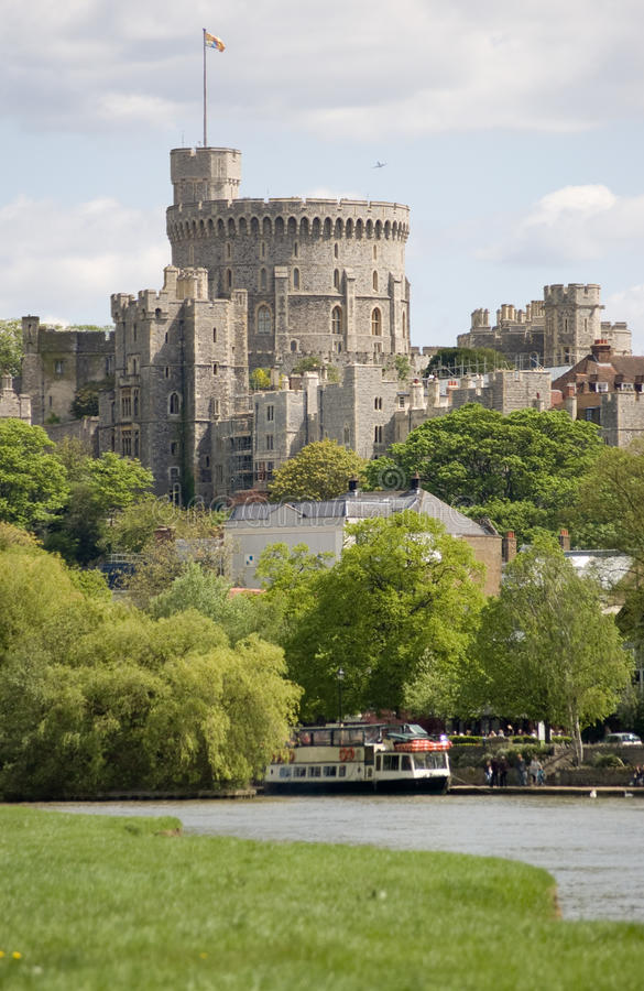 Windsor Castle and River Thames. View of the imposing Round Tower of Windsor Castle from the banks of the River Thames in Berkshire. The Royal Standard is flying stock photos