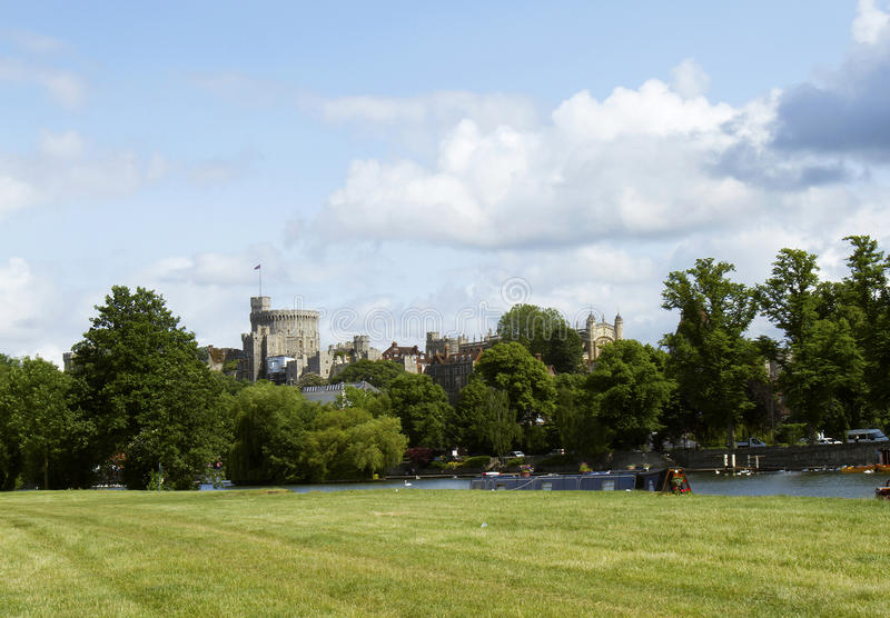 Windsor Castle from the Thames River. Windsor castle viewed from Thames River side park along entrance to town stock images