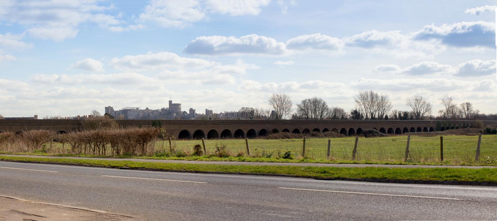 Windsor Railway Viaduct and Castle. View of the viaduct which carries the railway branch line to Windsor across the Eton flood plains. Windsor castle is visible stock photos
