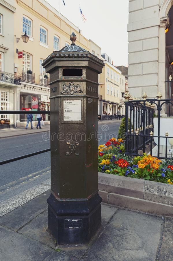 UK pillar box, a free-standing post box to be collected by the Royal Mail of United Kingdom, situated on High Street of Windsor. Windsor, UK - April 2018: Early royalty free stock images