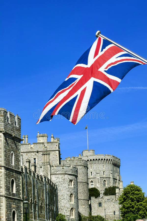 Windsor Castle with a Union Jack. Windsor, UK, May 22, 2010 : Windsor Castle with a Union Jack flying in the foreground which is a popular visitors attraction of royalty free stock images