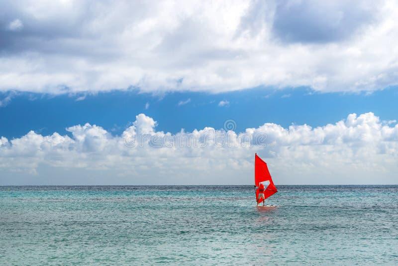Windsurf com vela vermelha Esportes de água em férias fotos de stock