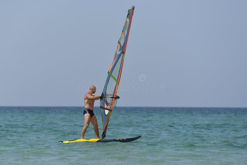 Windsurf del hombre de los deportes en el mar en un día soleado imagen de archivo libre de regalías