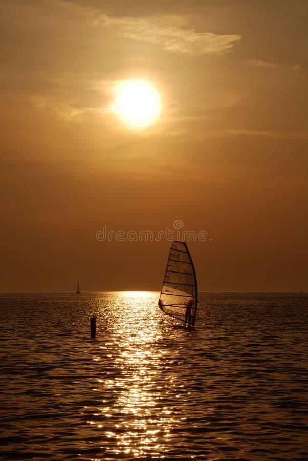 Windsurf sunset. Guy windsurfing during sunset in backlight - Portorose, Slovenia stock photo