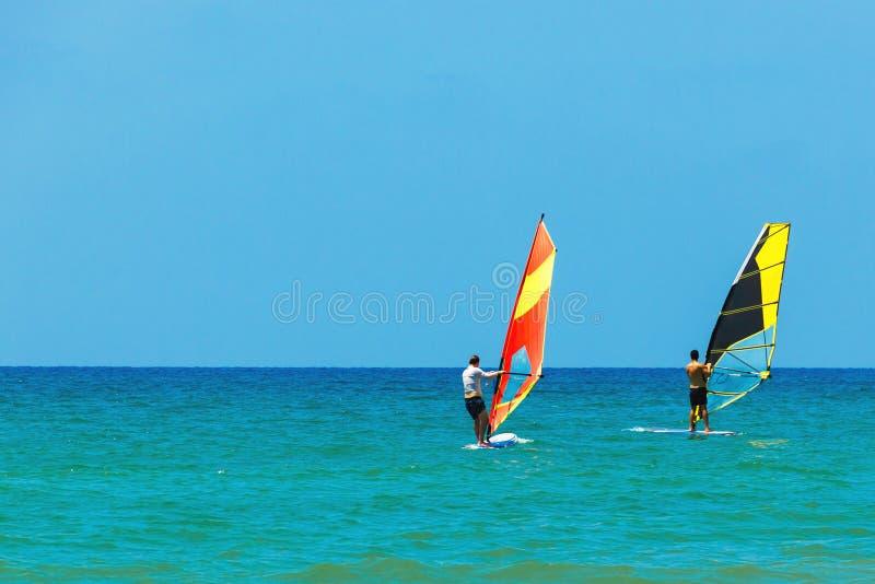 Windsurfen auf dem Hintergrund der Seelandschaft und des klaren Himmels Zwei Windsurfersmänner streben herein Sport, Kopienraum a lizenzfreies stockbild