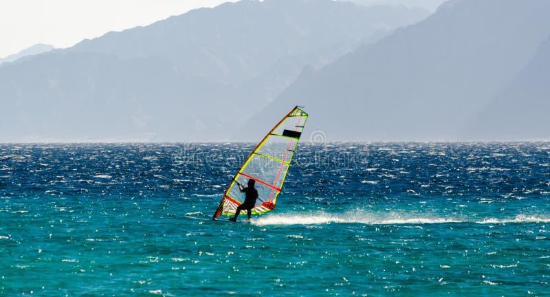 Windsurfer на предпосылке езд высоких гор на волнах Красного Моря в Египте Dahab южном Синай стоковая фотография