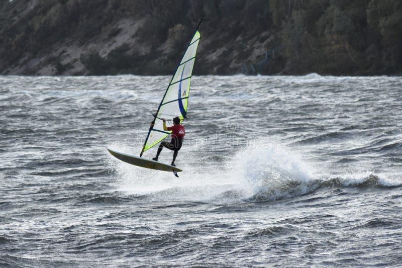 Windsurfer anónimo de salto en aguas tempestuosas del mar Báltico imagenes de archivo