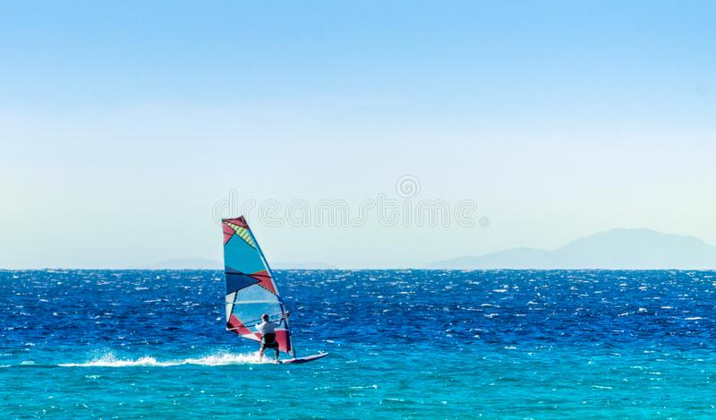 Windsurfer on the background of high mountains rides on the waves of the Red Sea in Egypt Dahab South Sinai. Windsurfer on the background of high mountains rides stock images