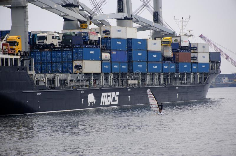 Windsurfer in contrast with giant container ship royalty free stock images