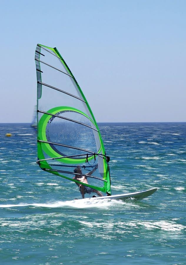 Windsurfer experimentado que apresura a lo largo del mar azul asoleado que da una sensación verdadera del movimiento. foto de archivo