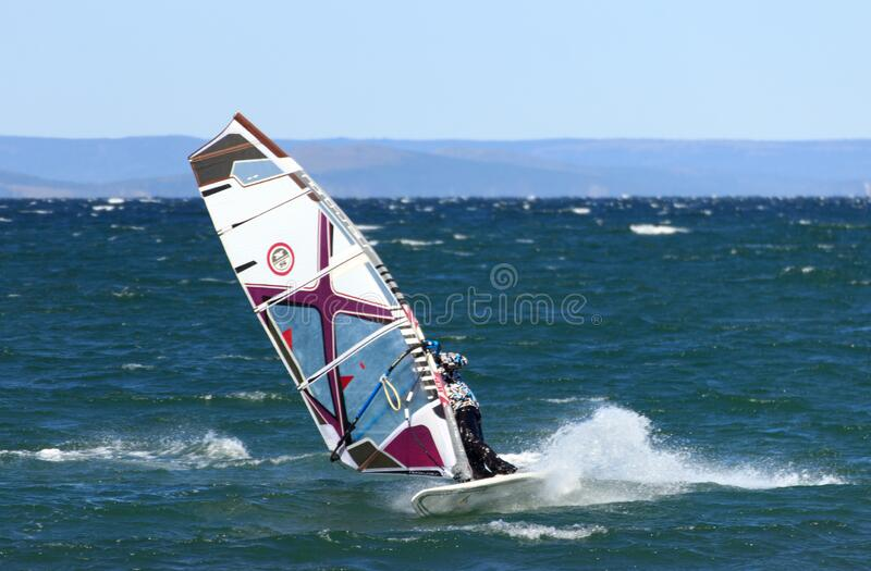 A windsurfer goes through a bend at high speed, riding in the waves with a autumn windy day. A windsurfer goes through a bend at high speed, riding in the waves stock photo