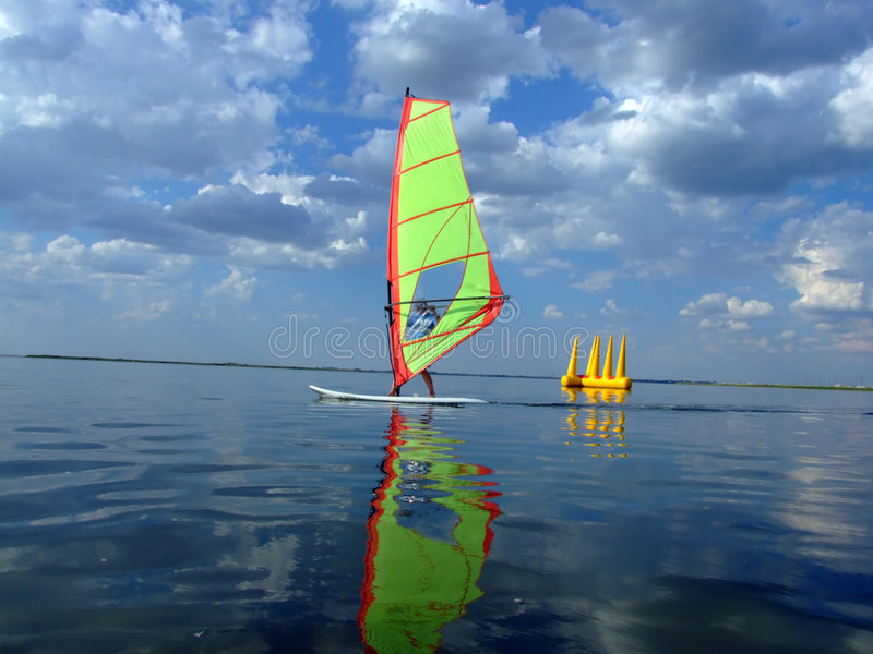 Windsurfer and its reflection. In water of a gulf royalty free stock photography