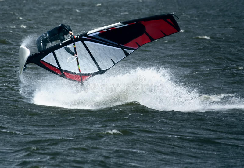 Windsurfer in Jump. Windsurfer Jumping on choppy Sea with spray stock image