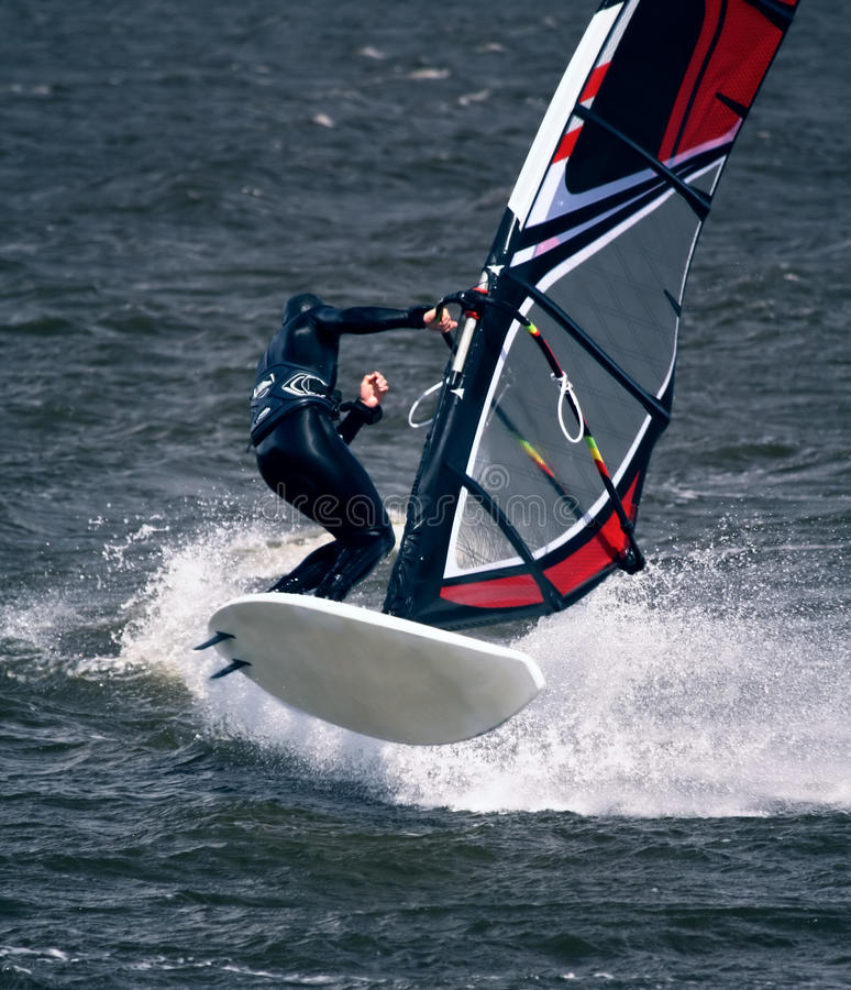 Windsurfer in Jump. Windsurfer Jumping on choppy Sea with spray stock images