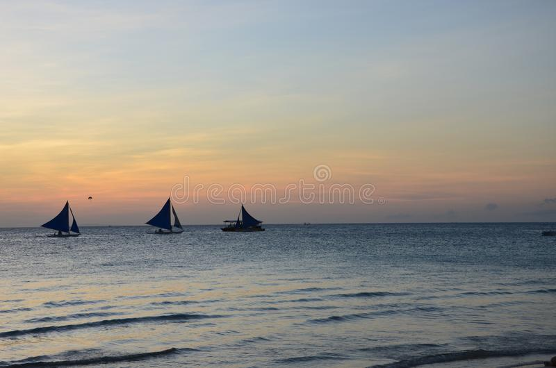 Windsurfer met het sunsetting in de horizon stock foto's