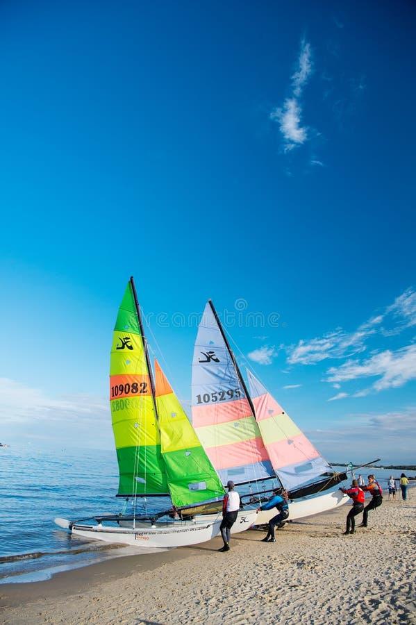 Windsurfer- oder Mannsportlerbrandungen und -segel an Bord stockfoto
