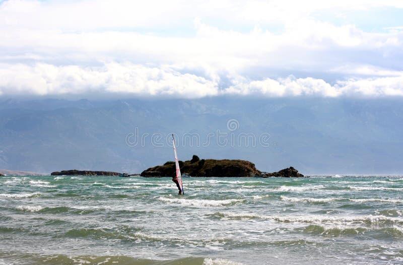 Windsurfer piegato su un mare vicino all'isola fotografie stock libere da diritti