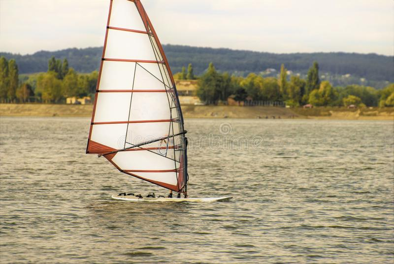 A pair of windsurfing plays in the waves, in the vastness of the reservoir stock image