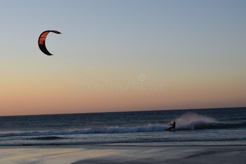 Windsurfer que practica surf en la playa en África en la puesta del sol foto de archivo libre de regalías